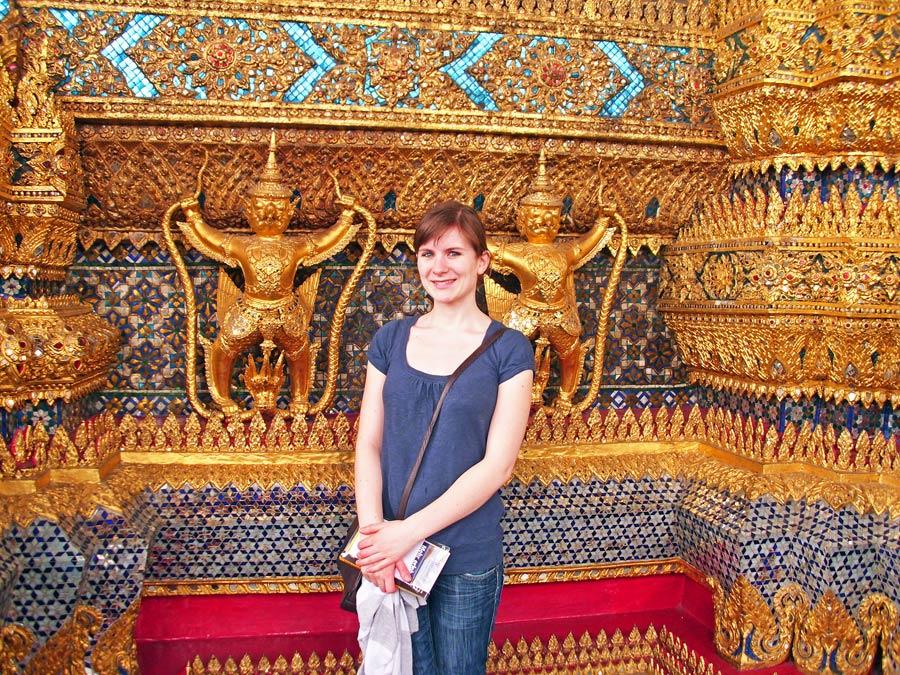 Anne in Jeans und T-Shirt vor einem wunderschönen Tempel in Thailand