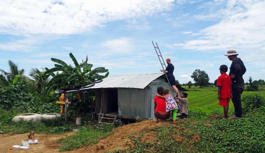 Sebastian installiert die Solaranlage und neugierige Nachbarn kommen um zu helfen.