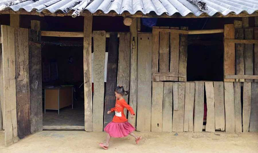Kleines Mädchen vor Schule in Vietnam