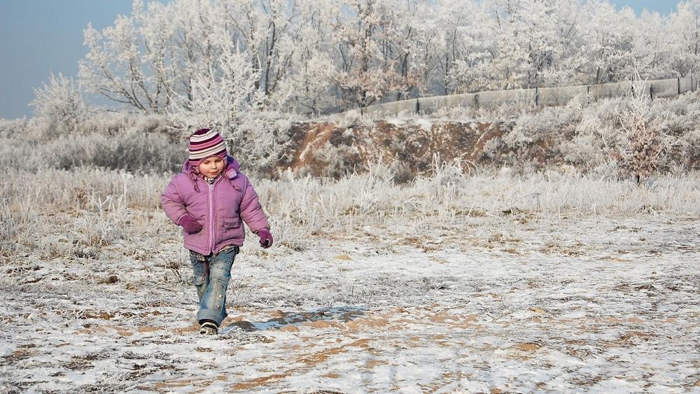 Kind läuft in Barfußschuhen im Winter