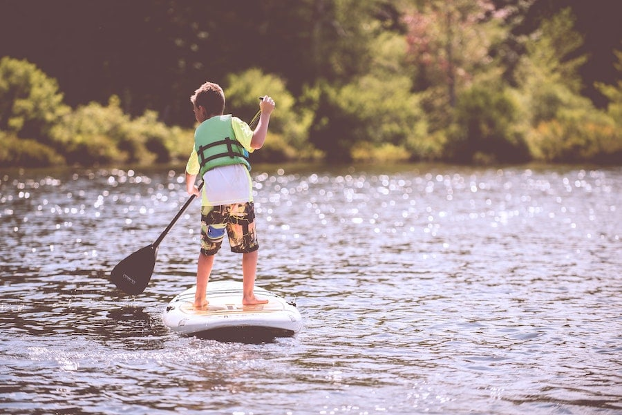 Junge mit SUP und Paddel auf dem See
