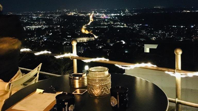 Beleuchtete Stadt abends mit Turmberg-Blick